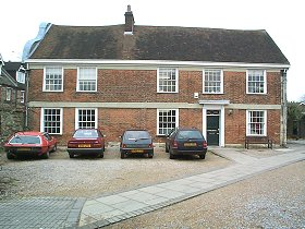The house is a two-storeyed red brick building of about 1665 with a Dutch gable on the west front. The east side is earlier, of stone with a 15th or 16th century window on the first floor.