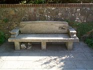 A little dog lies curled up beneath this fine stone bench seat.